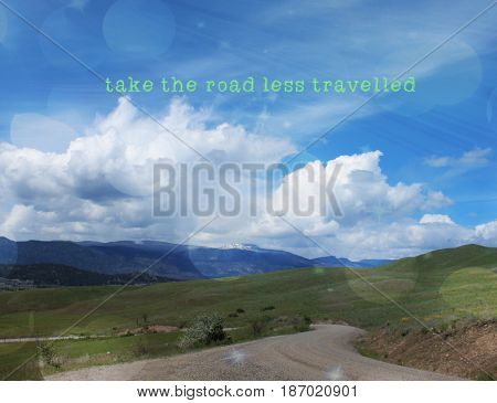 Conceptual landscape view with inspirational quote. Take the road less travelled. Lighting effects.
