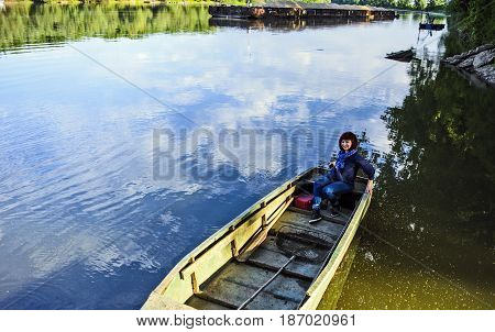 Young woman floats in the river in a fishing boat.