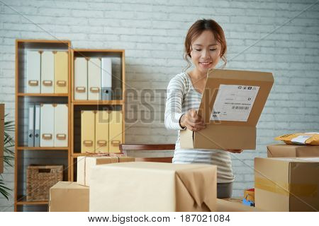 Happy Vietnamese young woman opening parcel she received