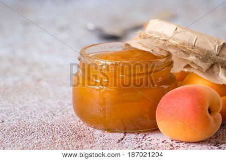 Freshly cooked dessert. Ripe apricots, a jar of jam and a spoon on a light background.