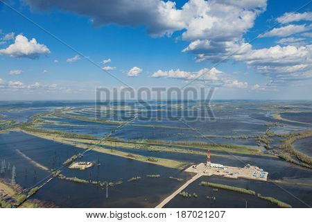 Oil rig in flood-land of great river during spring, aerial view