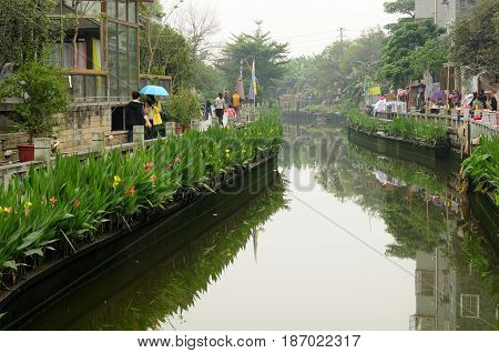 March 18 2017. Guangzhou China. Chinese visitors walking a water canal within the Huangpu Ancient Port market in the city of Guangzhou China in Guangdong province on an rainy overcast day.