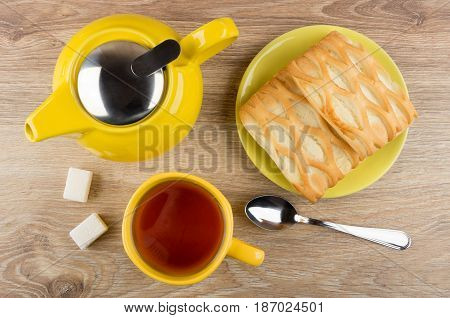 Tea In Cup, Spoon, Lumpy Sugar, Yellow Teapot And Pies