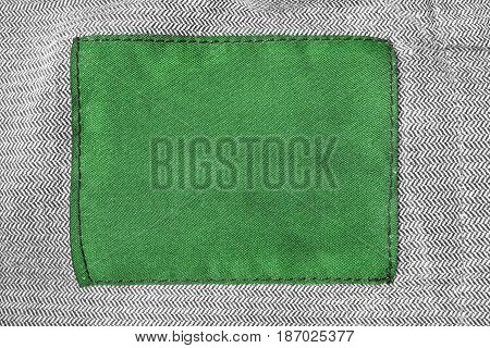 Green blank clothes label on gray tweed as a background