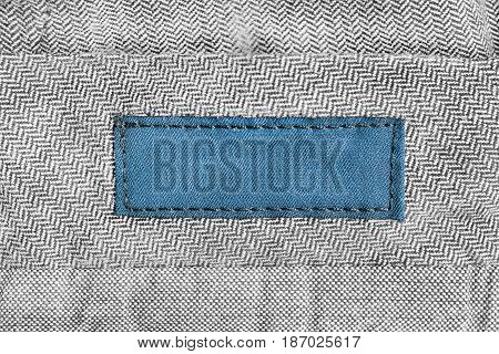 Blank blue clothes label on gray cloth as a background