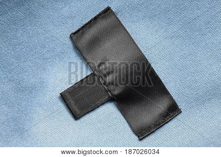 Black blank clothes label on blue denim as a background