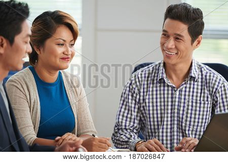 Cheerful mature Asian businessman discussing his idea with investors