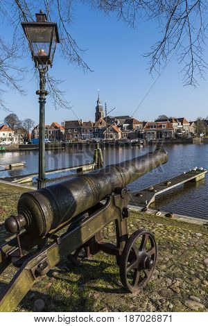 Harbor of Blokzijl in the province of Overijssel with canon and lantern and in the background the church old ship and old monumental houses The Netherlands.