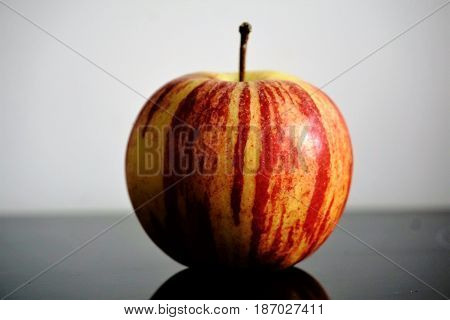 Photo of a single apple on a glass table