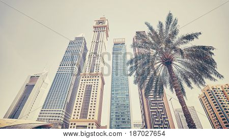 Retro Stylized Panoramic Photo Of Dubai Skyscrapers With A Palm Tree, Uae.