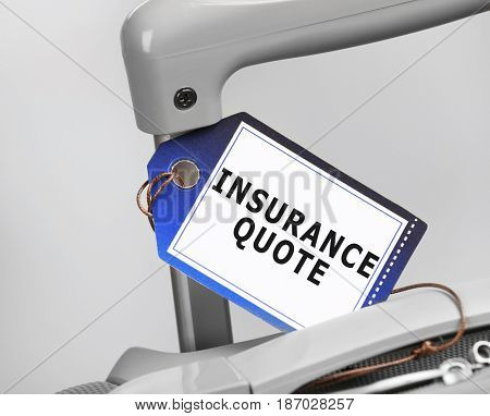 Insurance quote concept. Label with text on suitcase, closeup