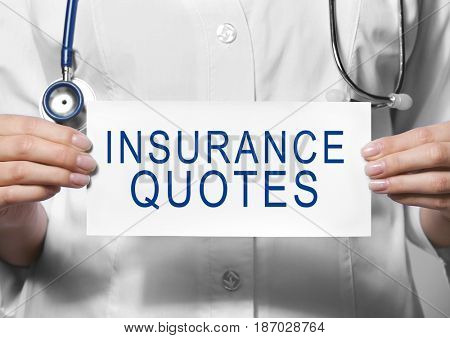Insurance quotes concept. Doctor holding paper with text in hands, closeup