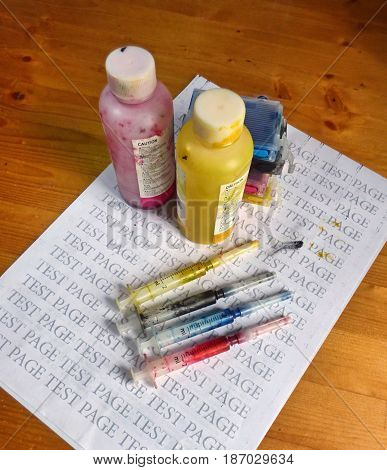 Set of Ink cartridges, refill paints in bottles and dirty syringes. On printed test page. Jet printer maintenance.