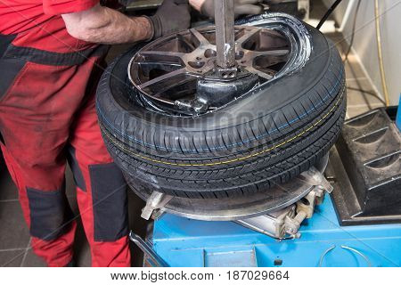 Man mounts new tyre on a rim in the car repair