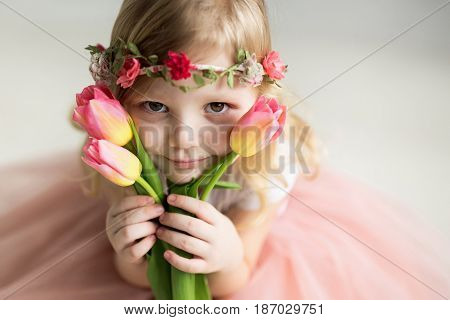 Beautiful girl with tulips on a light background