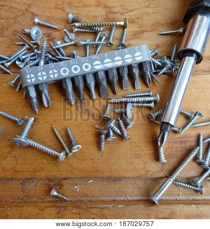 Screws, screwdriver and set of bits (heads) on wood background. Home improvement tools and fasteners. Selected focus on bits.