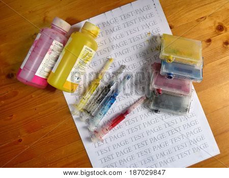Set of Ink cartridges and dirty refill syringes. On printed test page. Jet printer maintenance.