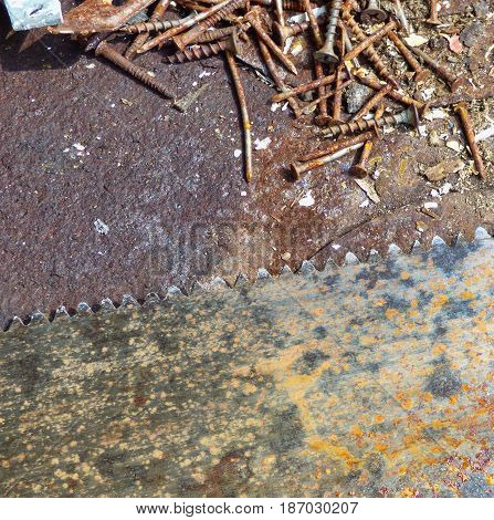 Old rusty texture with different screws and big saw blade. Aged metal - industrial background with place for text. Dirty steel surface in workshop. Top view.