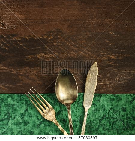 A square overhead photo of a vintage fork, knife, and spoon on a wooden background and green textile texture with a place for text. A restaurant menu or special offer banner design template