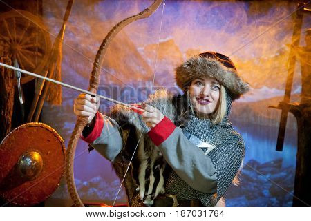 A woman in the costume of a warrior of the times of Kiev Rus in chain mail with a bow and arrow