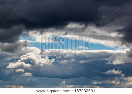 Blue sky surrounded by storm clouds in the middle of the day. Clouds illuminated by the sun