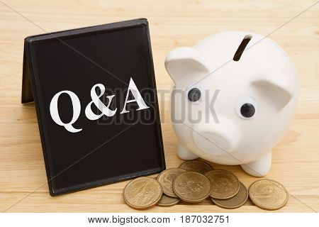 Getting answer to your money questions A piggy bank with retro freestanding chalkboard with gold coins on a wood desk with text Q&A
