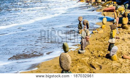 Stacked rocks on seashore in the sand