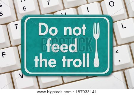 A teal sign with text Do not feed the troll and fork icon on a keyboard 3D Illustration