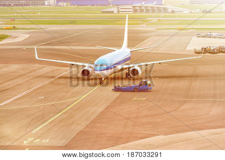 Airplane ready for take-off in a airport hub. Commercial passenger airplane during push back operation.