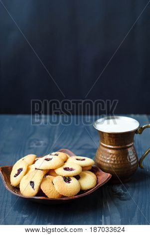 Shortbread cookies and milk in an oriental copper mug. Eastern cookies on a dark background and a copper glass with milk. Homemade cookies and milk. Cookies Lady fingers .