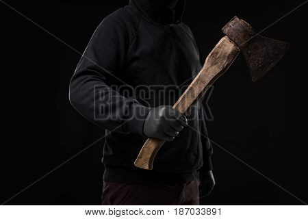 A man in gloves holds an ax in his hands against a black background. Criminal