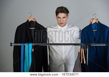 Shop Assistant Or Confident Businessman In Shirt Choosing Jacket