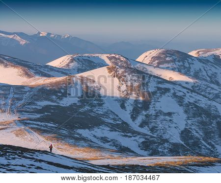 Hiker stays on a hill in a carpathian mountain valley covered with snow. Winter Carpathians Ukraine Europe
