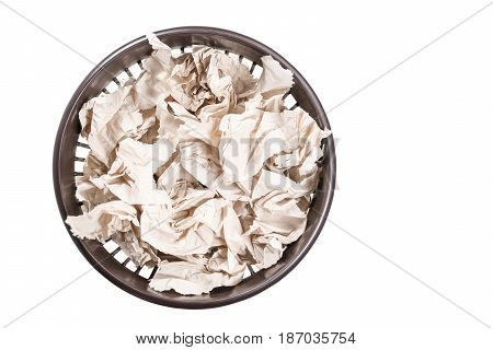 Crumpled toilet paper in a crowded trash can, top view, isolated on white background
