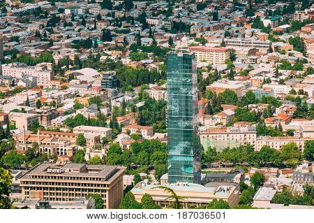 Tbilisi, Georgia - May 20, 2016: Aerial View Of New Glass Skyscraper Of The Biltmore Hotel, Surrounded By Buildings Of Soviet Time In Sunny Summer Day.