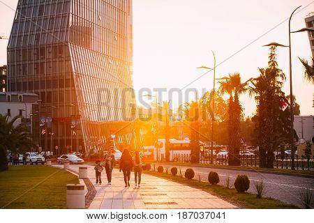 Batumi, Adjara, Georgia - May 27, 2016: People walking on Gogebashvili street near building Radisson Blu hotel at sunset.