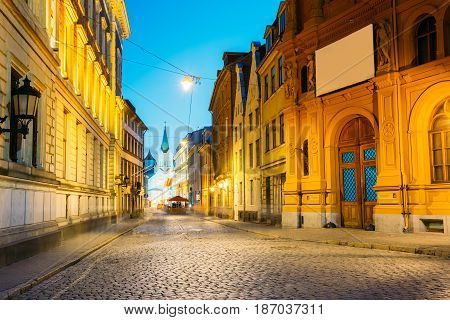 Riga, Latvia. Evening View Of Deserted Pils Street With Ancient Architecture In Bright Warm Yellow Illumination Under Summer Blue Sky. Our Lady Of Sorrows Or Virgin Of Anguish Church In The Distance.