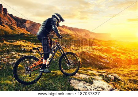 Ryder in full protective equipment on the mtb of two pendant bicycles rides along the green grass towards the sunset in the rays of the sunset sun against the backdrop of a landscape of rocky terrain under the setting sun and clouds.