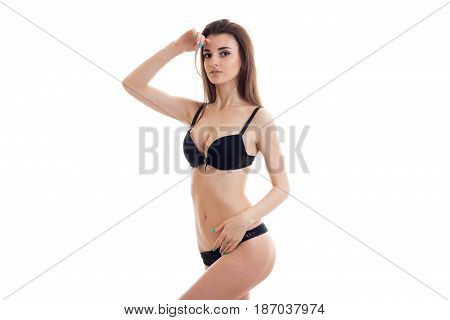 beautiful slim girl with big natural breasts in black lingerie has raised her hand to her face and posing for the camera isolated on white background.