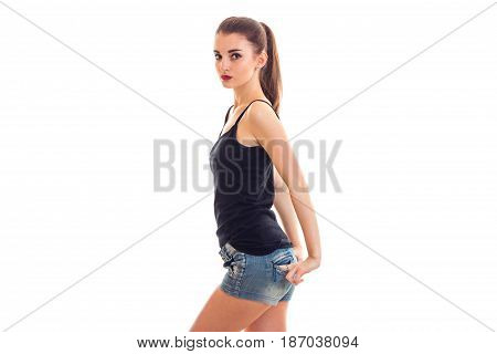 young slim sweet girl stands sideways in a t-shirt and keeps her hands in his pockets in shorts is isolated on a white background