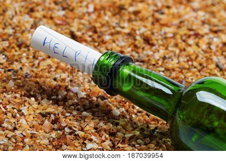 Bottle of wine with help message on sand in beach at sun summer day. Close-up view.