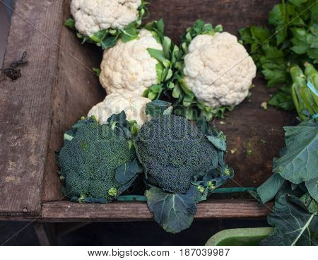 View of organic broccoli and cauliflower on wooden case