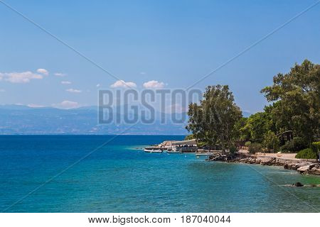 Coast landscape with stony beach, city and blue sea