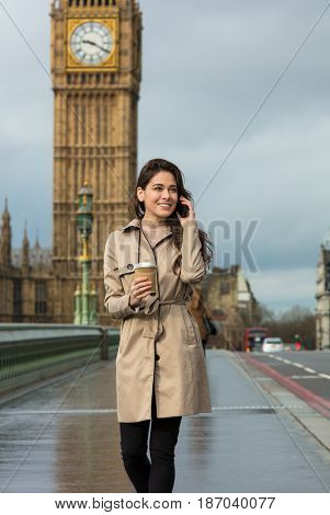 Girl or young woman walking across Westminster Bridge drinking coffee in a disposable cup and talking on a mobile cell phone with Big Ben in the background, London, England, Great Britain