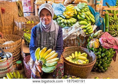 JAVA, INDONESIA - DECEMBER 18, 2016: Woman selling bananas on the local market on 18th december 2016 in Java Indonesia