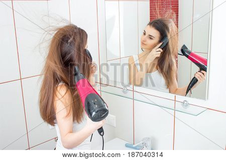 young cute girl looks in the mirror and and drying long hair closeup