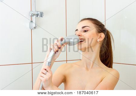 beautiful fun girl stands in the bathroom and sings in the shower spray close-up
