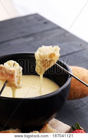 Gourmet Swiss Fondue Dinner With Assorted Cheeses On A Board And
