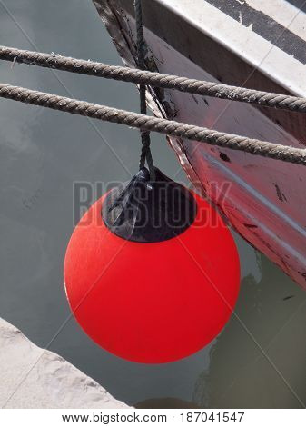 Red fenders placed between a boat and the dock