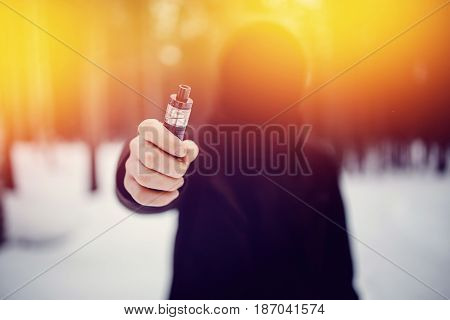 vaping man holding a mod device. cloud of vapor. Concept of giving up tobacco, using electron mod e-cig. High contrast and light